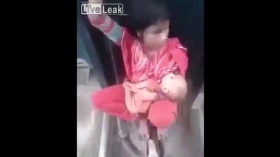 หญิงอินเดียยากจนอุ้มลูกแอบนั่งบนข้อต่อระหว่างโบกี้รถไฟ
